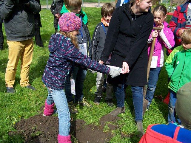 Safia und Keira vom Kinderrat versenken den Grundstein.